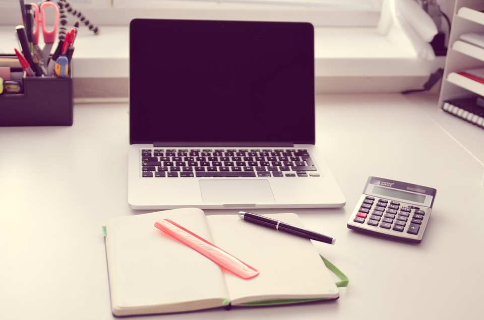 blank notebook, calculator and laptop computer used for severance pay calculator