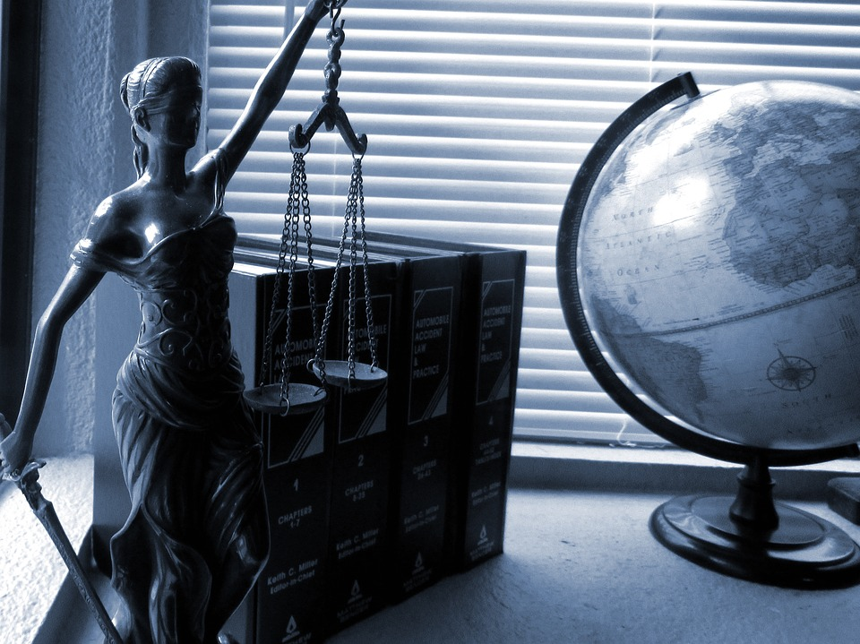 : legal books and statue of lady justice on an employment lawyer's desk